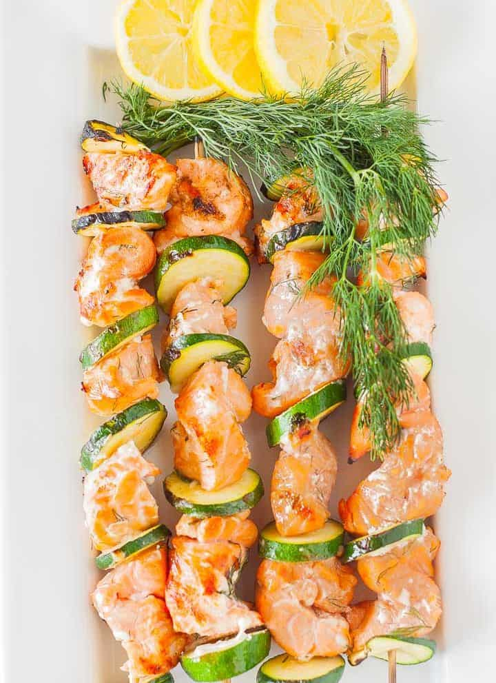 Four grilled salmon kabobs on a plate