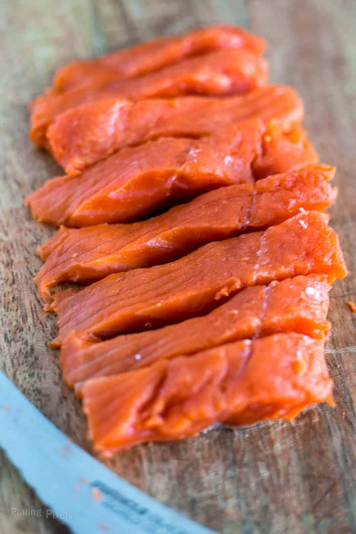 Slices of salmon a a cutting board to make kabobs