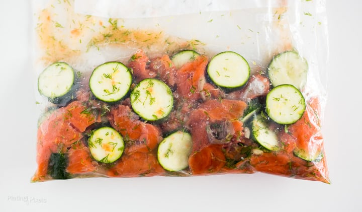 Salmon and zucchini slices marinating in a Ziploc bag