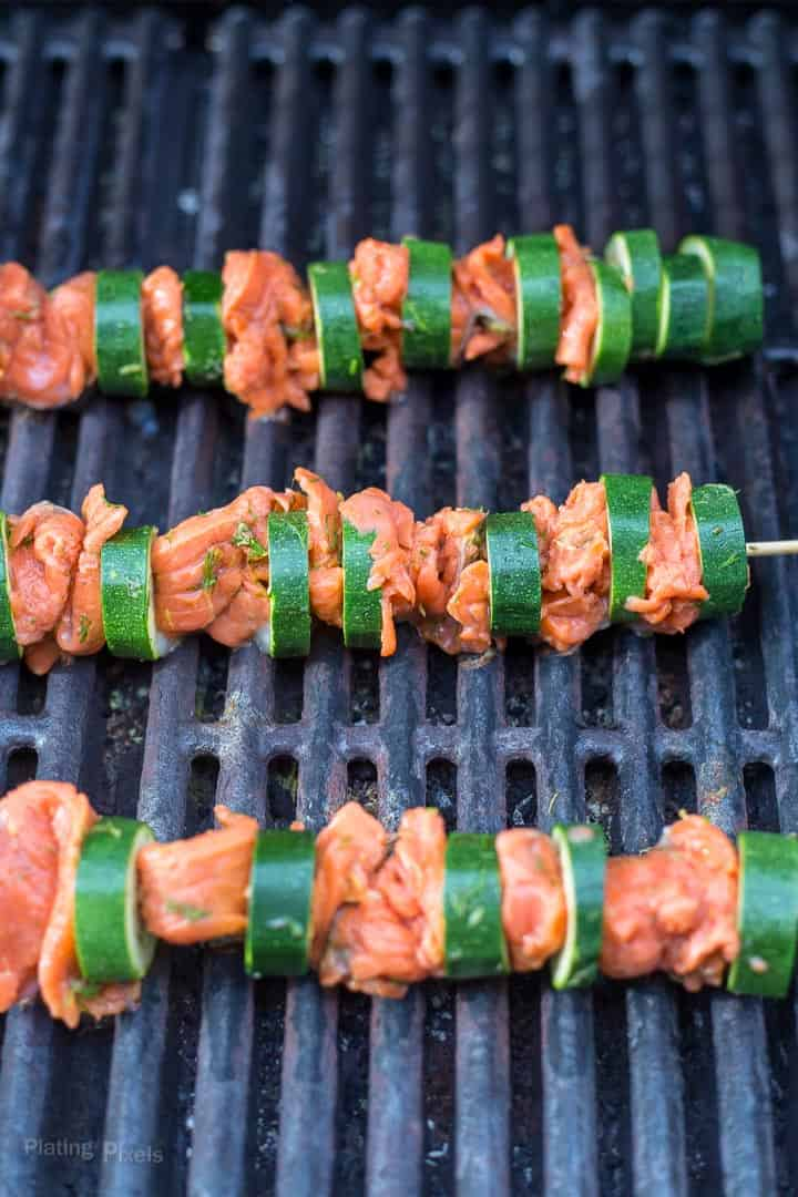Salmon on skewers with zucchini cooking on a gas grill