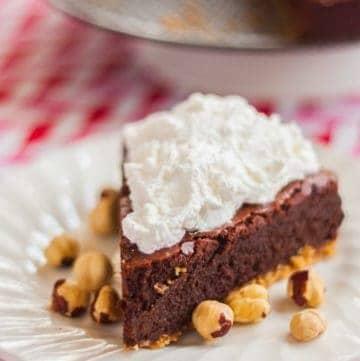 Chocolate Hazelnut Fudge Cake on a white plate with hazelnuts