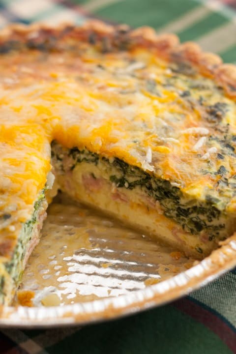 Mushroom, Spinach, and Ham Quiche in a pie pan with a slice cut out of it
