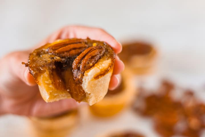 A hand holding Pecan Cookie Cups with caramel oozing out the middle