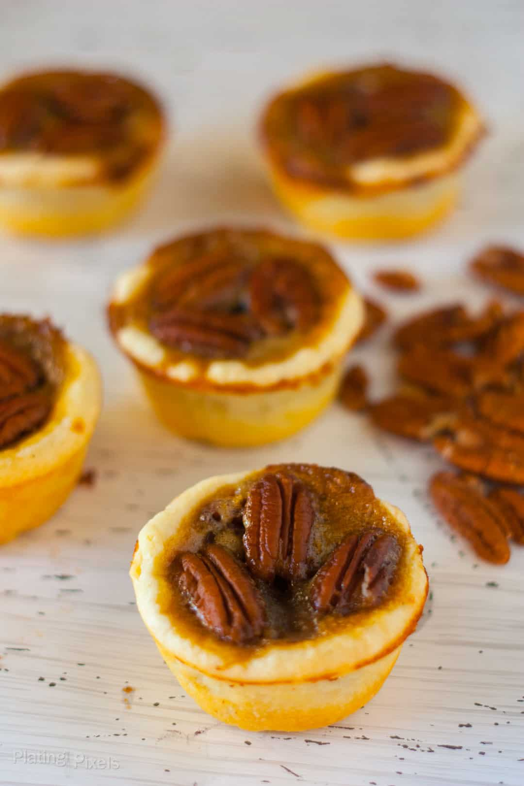 Pecan Tassies on a white table with pecans in background