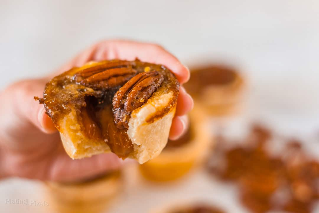 Hand holding a pecan tassie with a bite taken out of it and caramel filling oozing out
