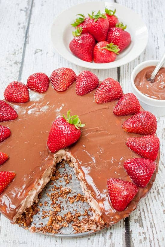 No Bake Chocolate Pudding Cheesecake topped with strawberries on a white table with slice cut out