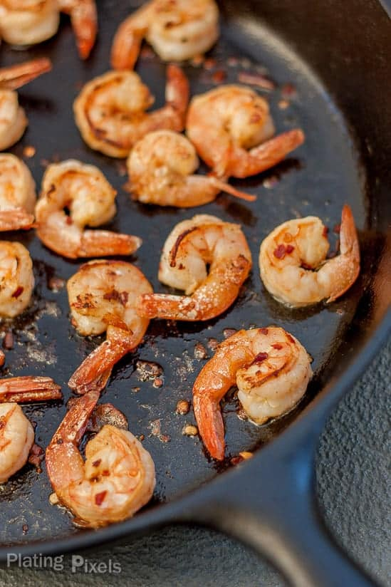 Process shot showing shrimp cooking in a pan