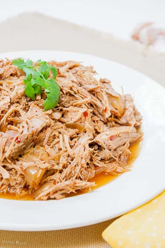 Carolina Style Slow Cooker Pulled Pork on a plate with a parsley garnish