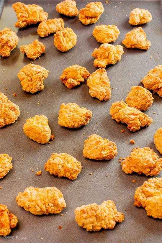 Just baked breaded chicken nuggets on a baking sheet