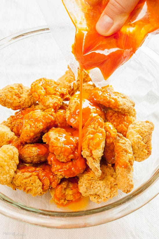 Pouring buffalo sauce over breaded chicken in a large glass bowl
