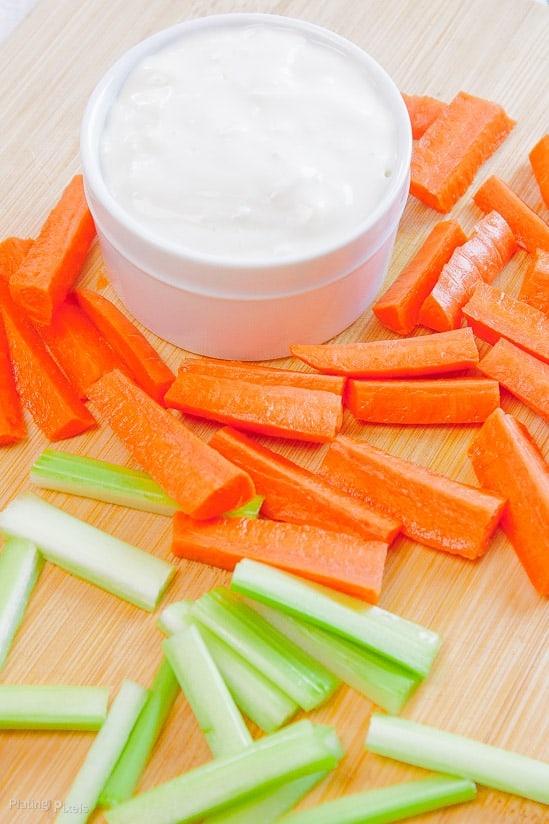 Blue cheese dressing for dipping with carrot and celery sticks on a cutting board