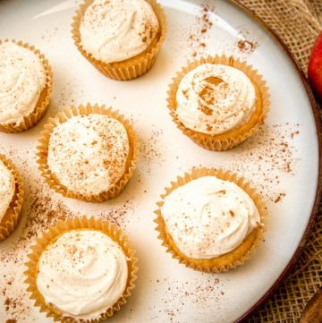 Spiced Apple Cider Cupcakes on a plate topped with cinnamon