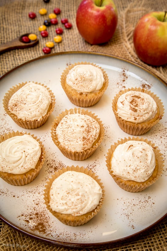 Seven Spiced Apple Cider Cupcakes on a plate with fresh apples in background