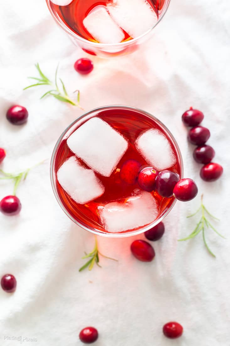 An overhead shot of an Apple Cranberry Ginger Ale Spritzer garnished with fresh cranberries