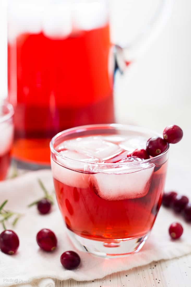 A close up of an Apple Cranberry Ginger Ale Spritzer in a small glass with ice