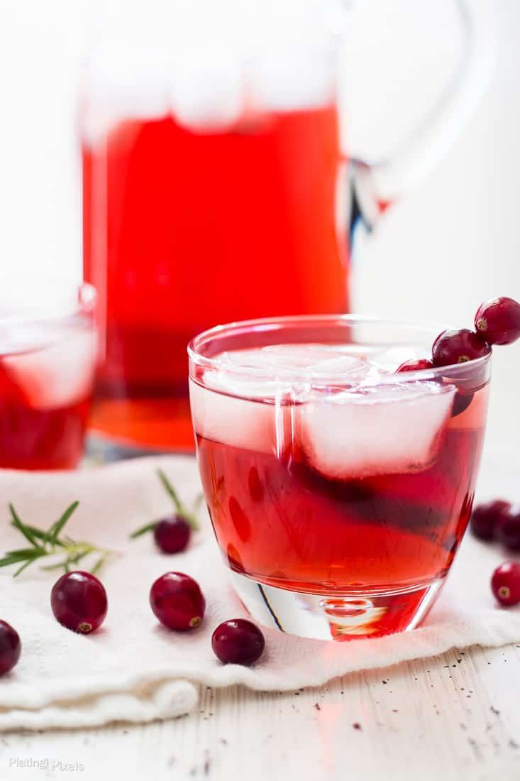 An Apple Cranberry Ginger Ale Spritzer in a glass with fresh cranberries scattered around