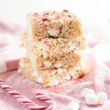 Three stacked Brown Butter Peppermint Rice Krispie Treats with candy cane decorations