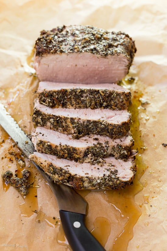 Garlic Herbed Pork Loin on a cutting board cut into slices