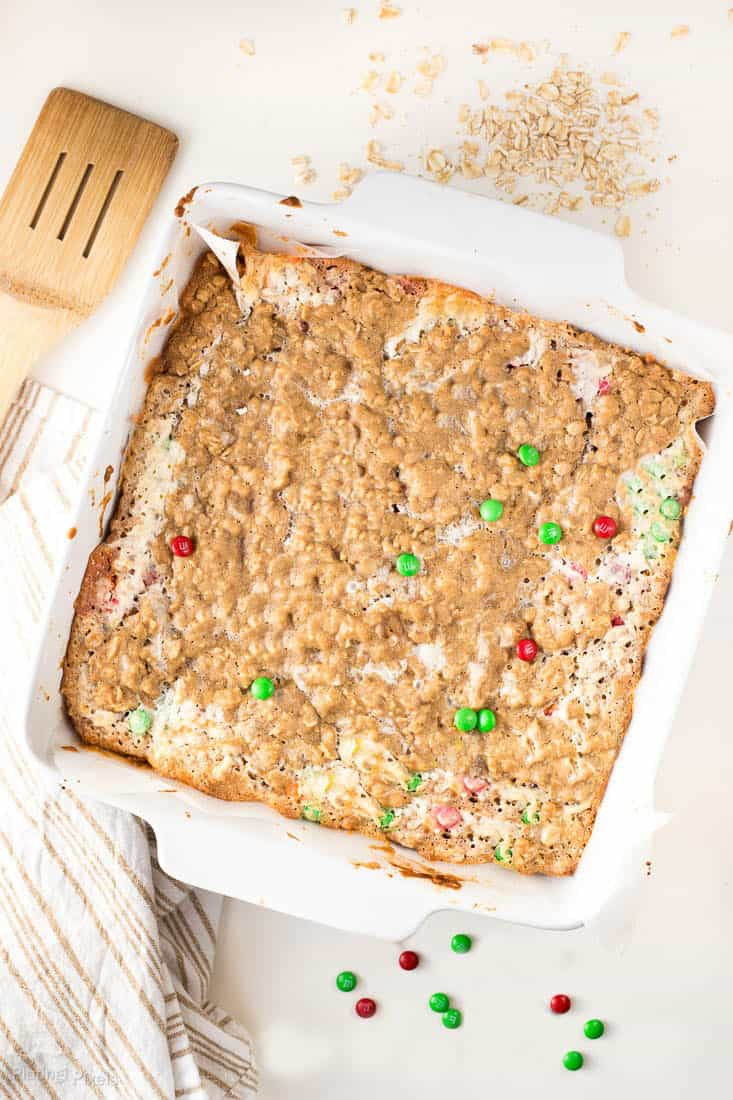 Chewy Coconut Chocolate Oatmeal Bars in a white square dish topped with red and green m&m's
