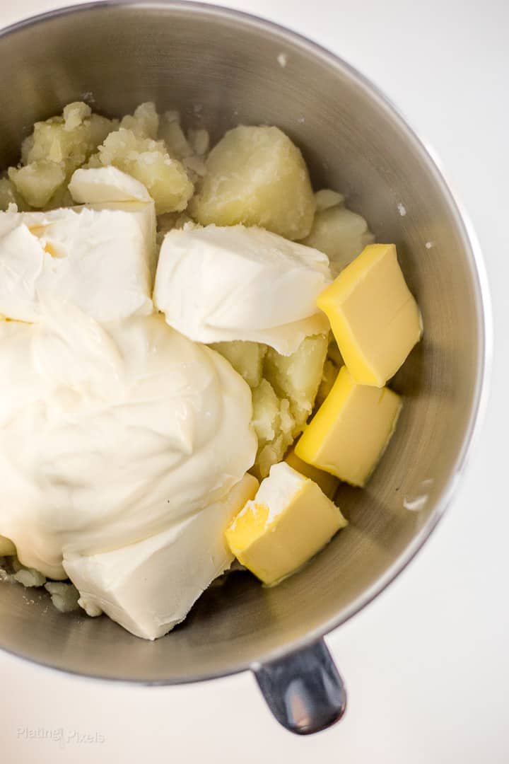 Potatoes, sour cream, butter, cream cheese and milk in a metal mixing bowl