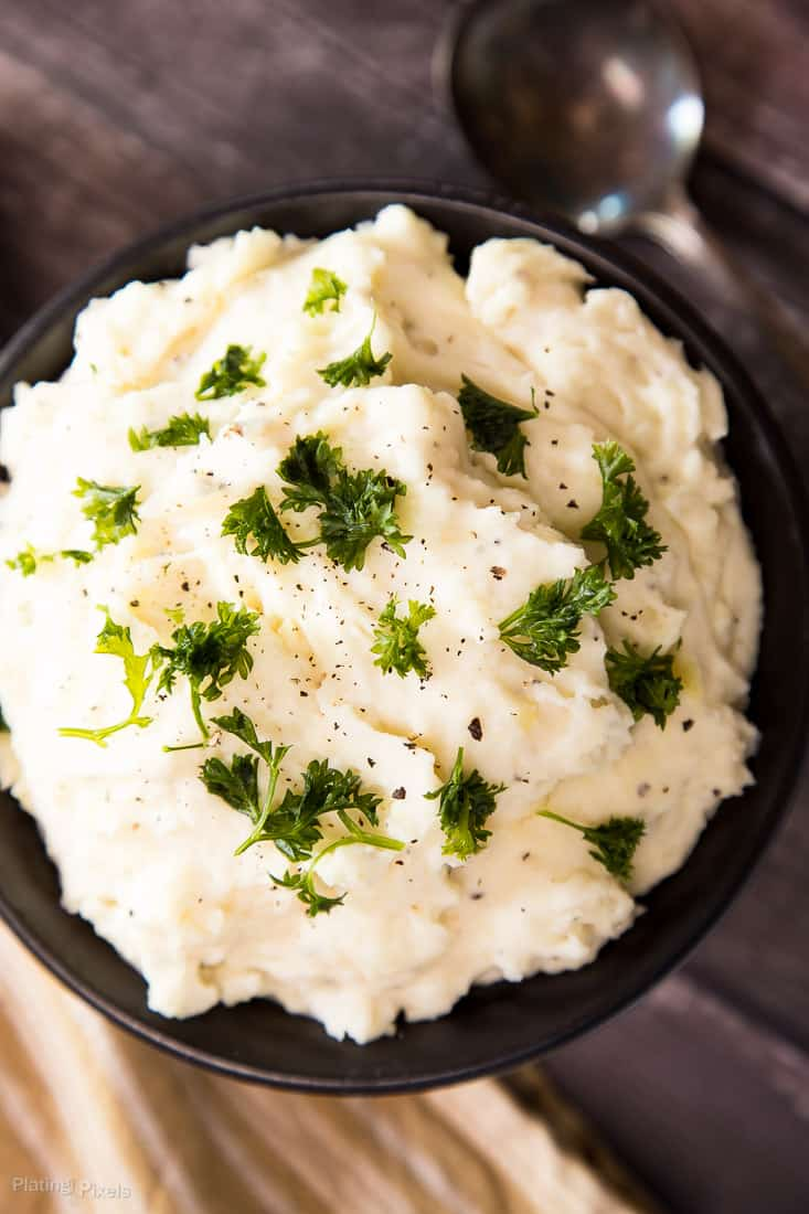 A close up of Creamy Mashed Potatoes in a black bowl garnished with parsley
