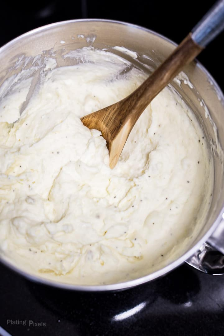 Stirring Creamy Mashed Potatoes in a large metal bowl with a wooden spoon