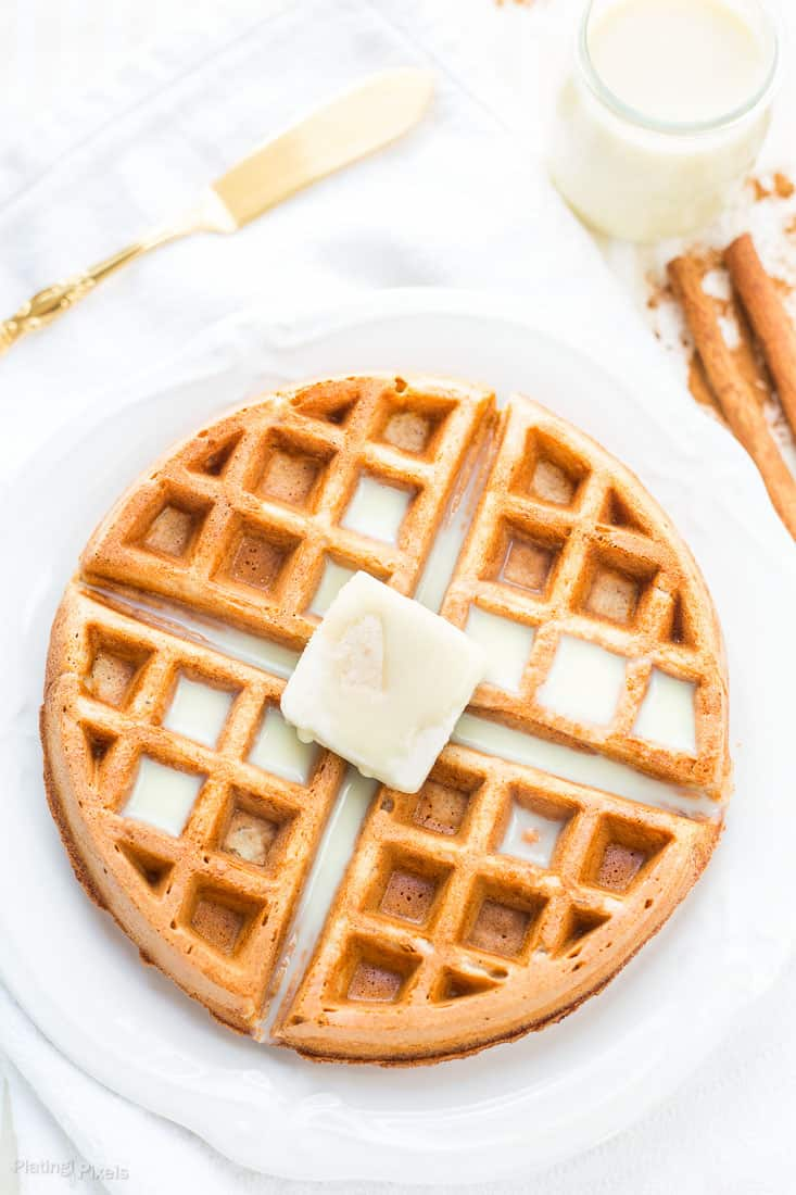 An overhead shot of Eggnog Waffles on a plate topped with butter
