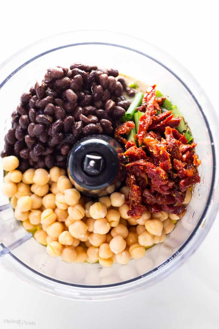 An overhead shot of ingredients to make Sun Dried Tomato Black Bean Hummus in a food processor