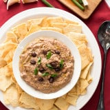 Sun Dried Tomato Black Bean Hummus in a bowl with chips around it and garlic cloves at the side