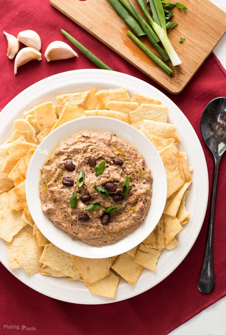 An overhead shot of Sun Dried Tomato Black Bean Hummus in a bowl with chips