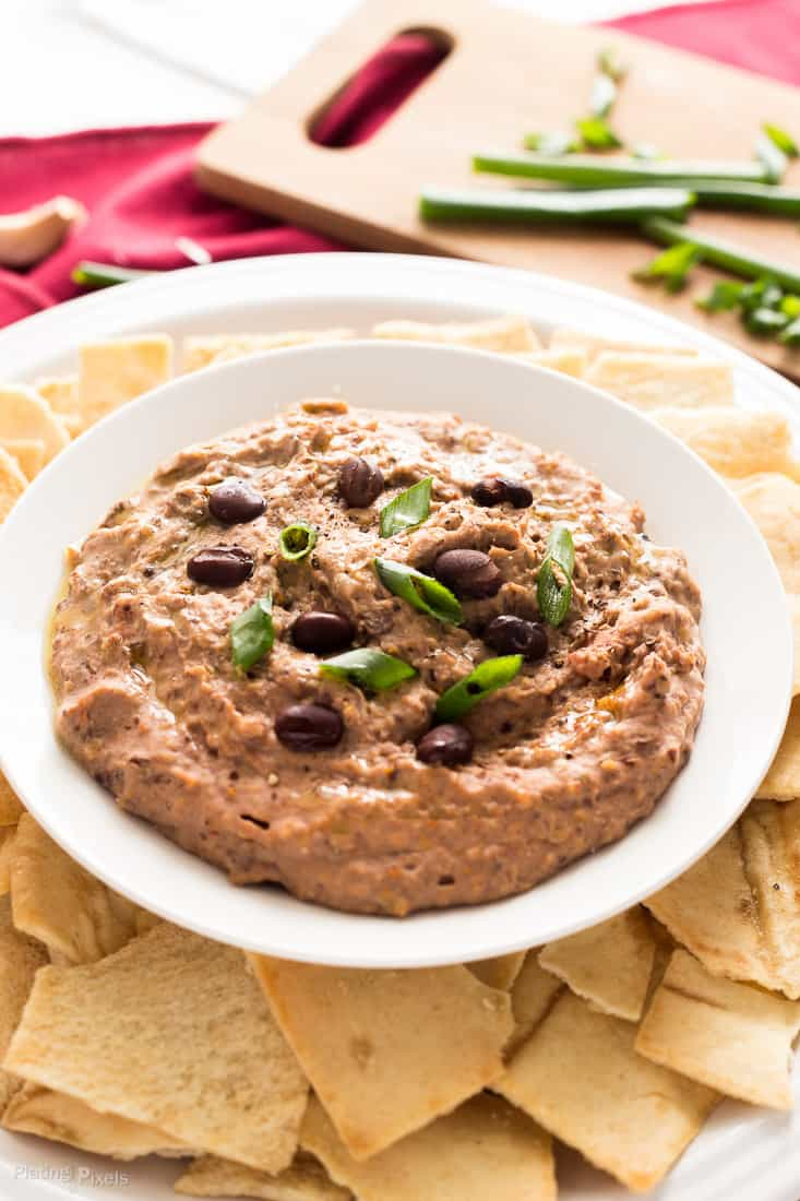 A close up of Sun Dried Tomato Black Bean Hummus in a bowl with chips around it and garnished with green onions