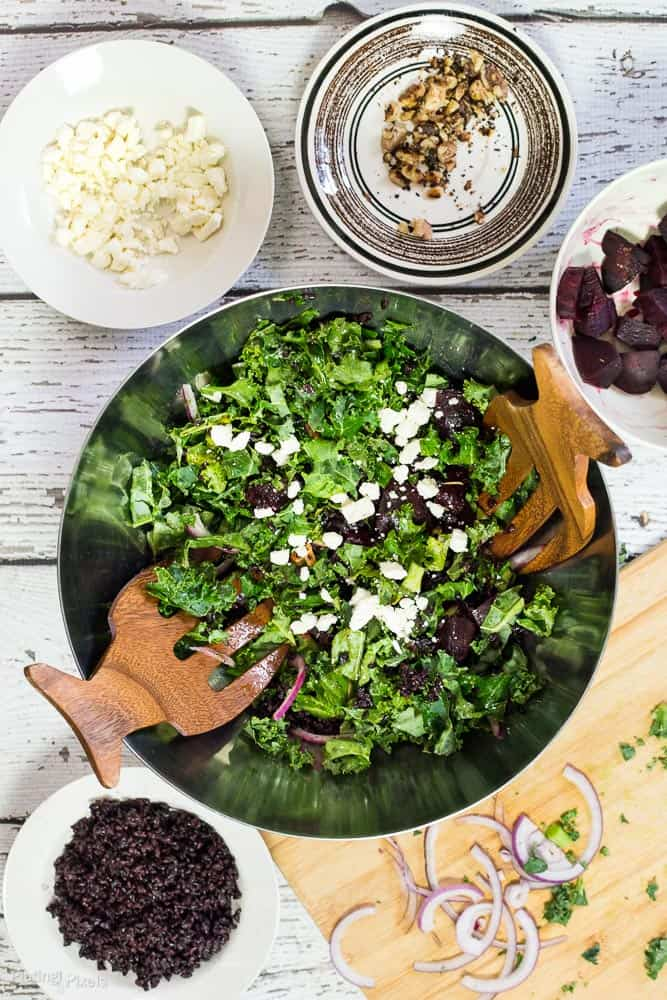A roasted beet and kale salad in a large serving bowl with ingredients all around it