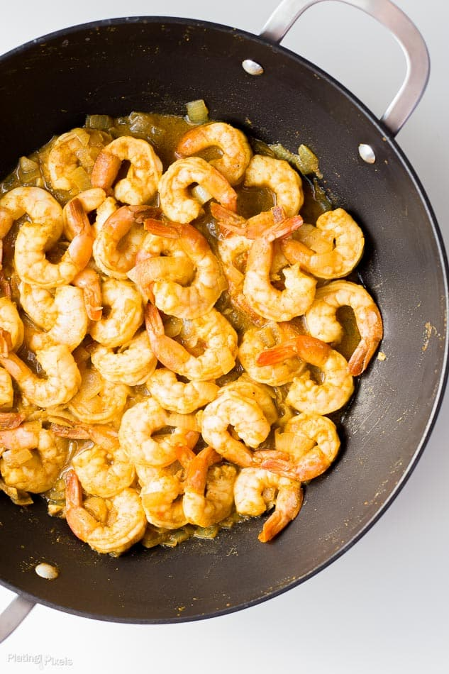 Process shot of Coconut Curry Shrimp cooking in a wok