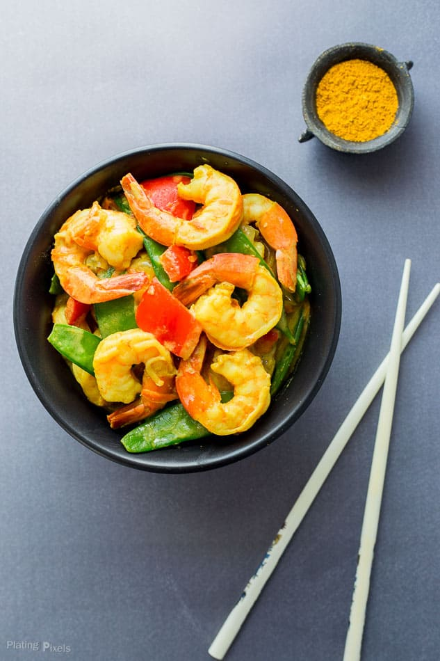 An overhead shot of prepared Coconut Curry Shrimp in a black bowl with veggies next to chop sticks