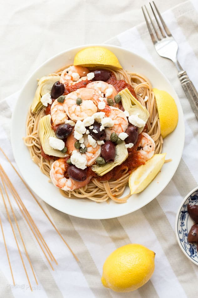 Overhead shot of a bowl of Mediterranean Shrimp Pasta with lemon wedge garnishes