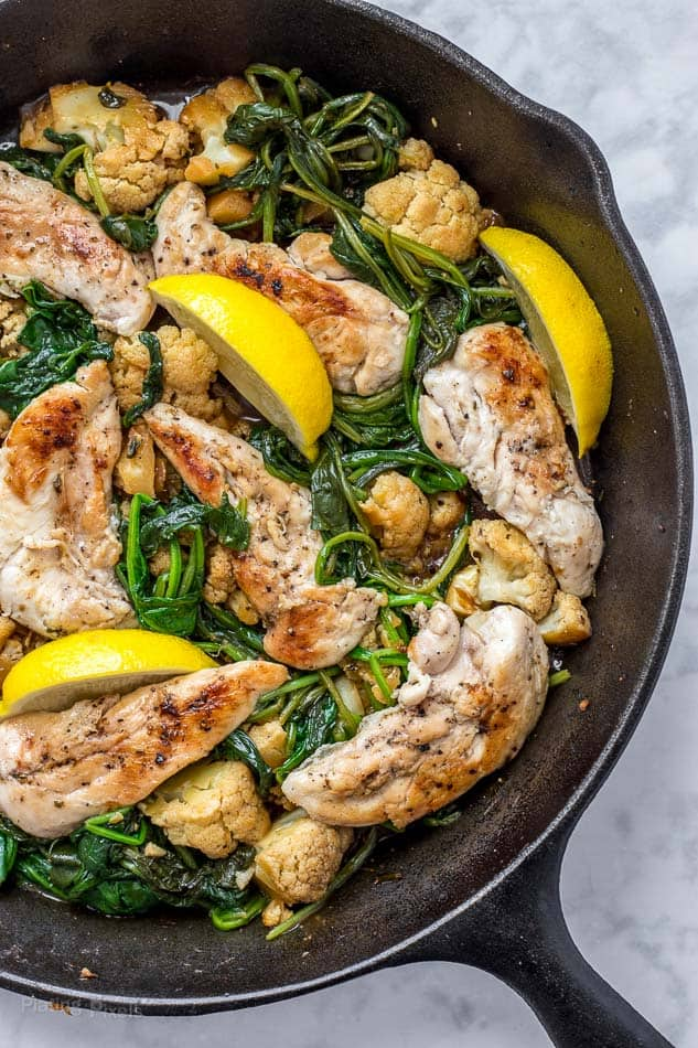 Process shot of lemon chicken cooking in a skillet with wedges of lemon and spinach