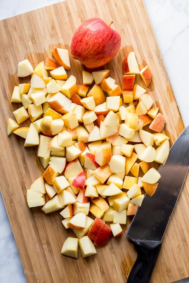 Cutting gala apple into small pieces on a cutting board