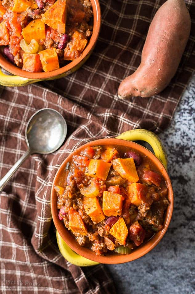 An overhead shot of roasted sweet potato chili in two small bowls with a spoon at the side