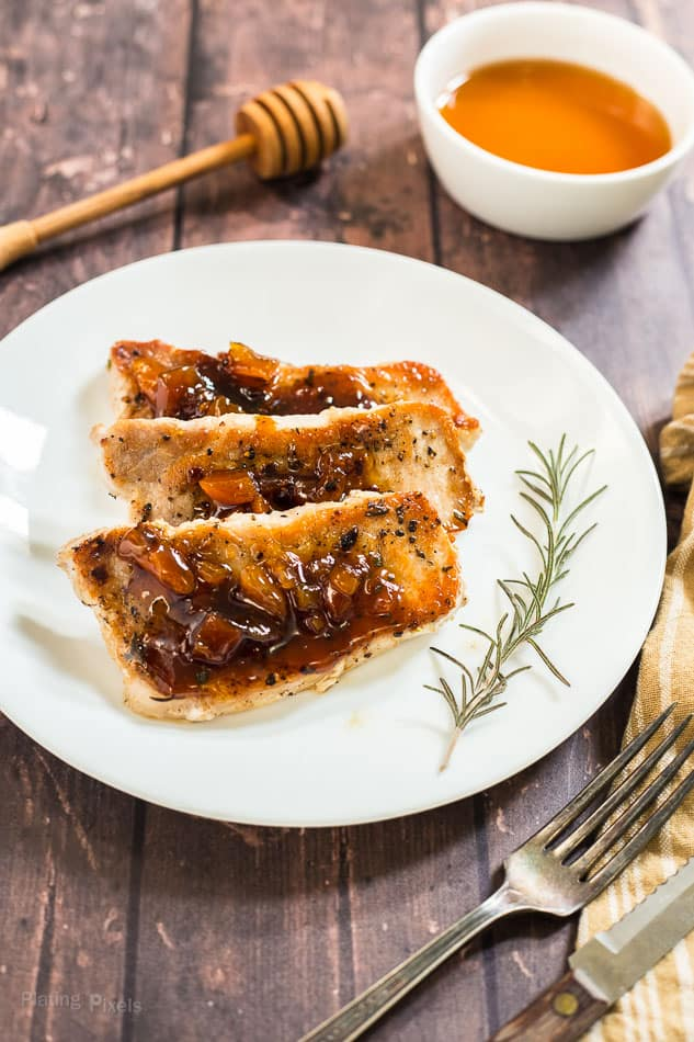 Honey Apricot Pork Chops on a white plate with the sauce in the background