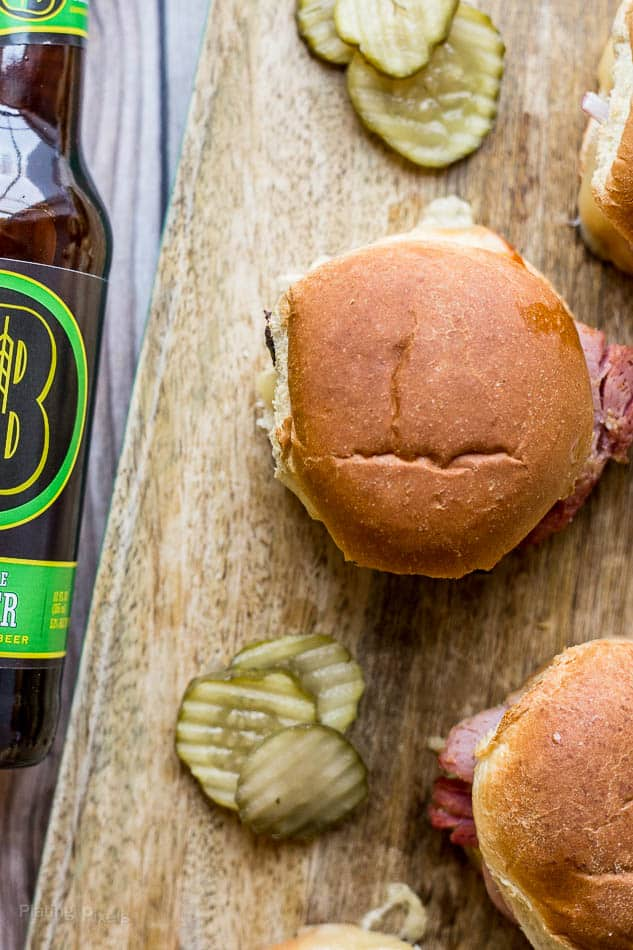 A close up of Ham and Gruyere Sliders on a wooden board with beer and pickles