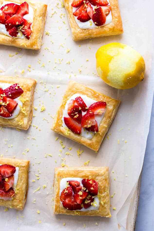 Six Strawberry Lemon Cream Breakfast Tarts on a baking sheet with halfway zested lemon