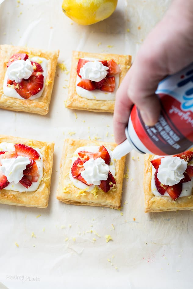 Garnishing Strawberry Lemon Cream Breakfast Tarts with can of whipped cream