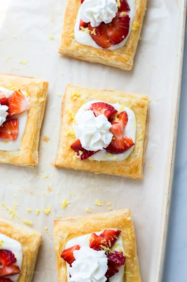 Five Strawberry Lemon Cream Breakfast Tarts on parchment paper with sprinkles of lemon zest