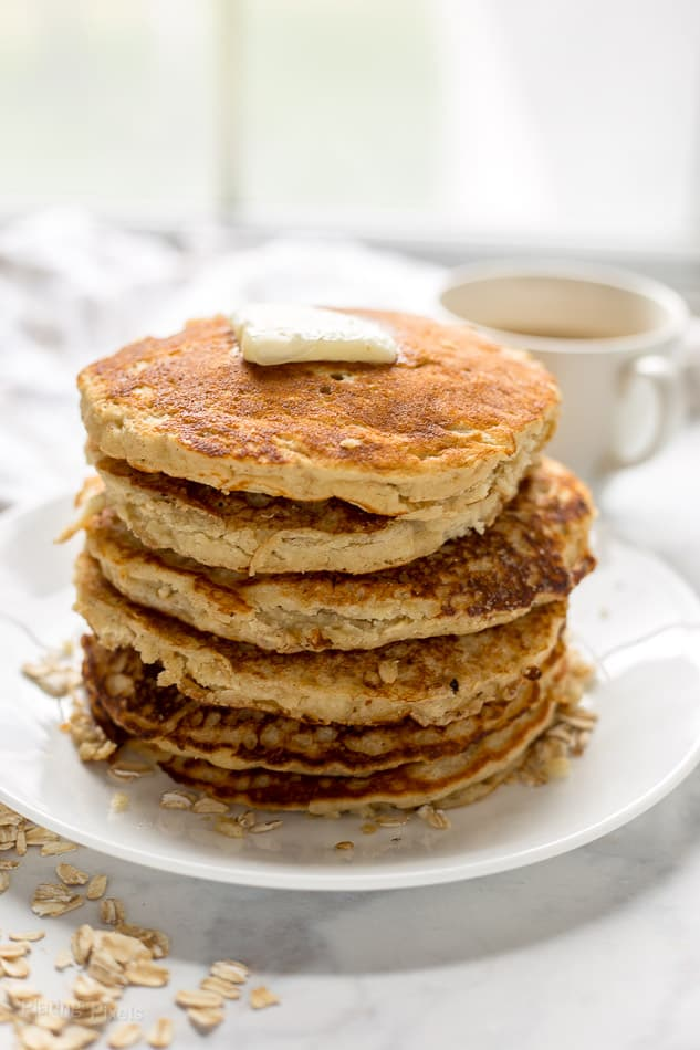 A stack of Banana Oatmeal Pancakes on a plate topped with butter