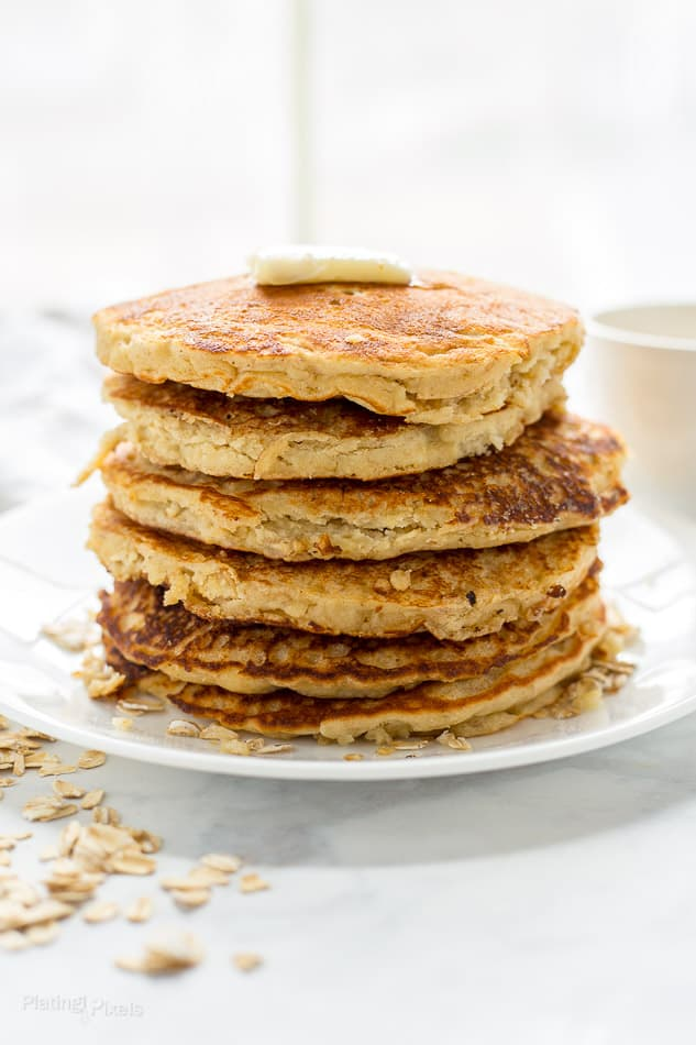 A close up of a stack of healthy Banana Oatmeal Pancakes on a plate next to window