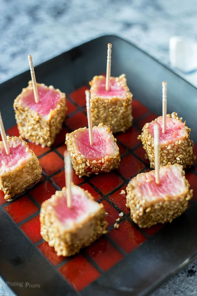 Seven Cooked Sesame Seared Ahi Tuna Bites on a black plate with toothpicks inserted in them