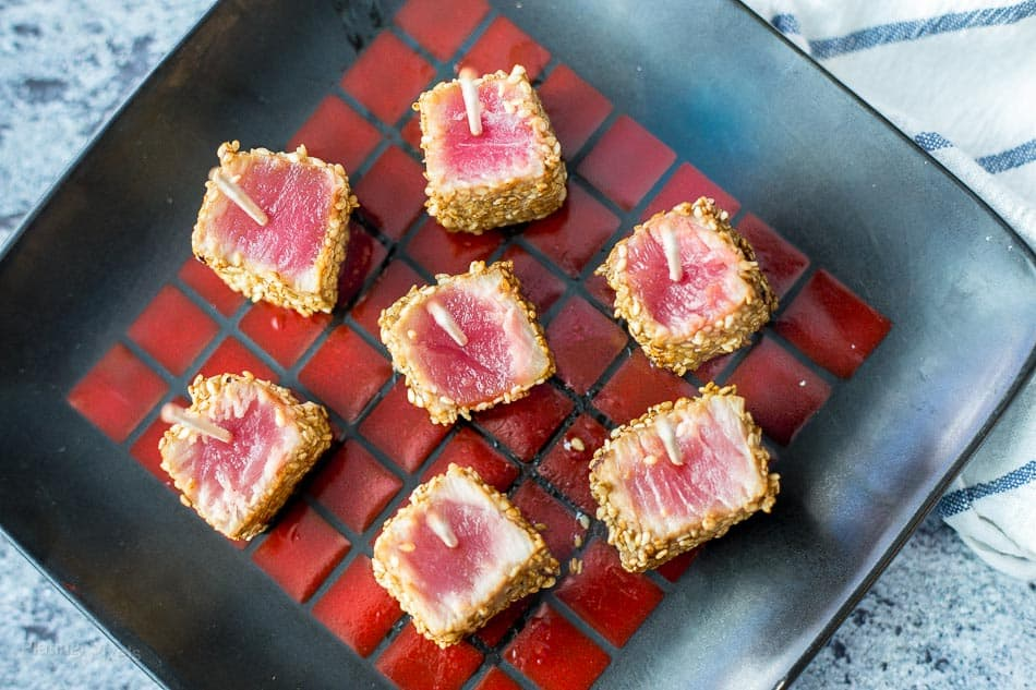 Ready to serve Sesame Seared Ahi Tuna Bites on a black and red square plate