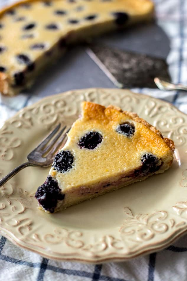A slice of Blackberry Custard Pie on a plate with a fork