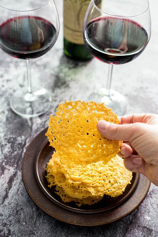 Hand holding a Parmesan Crisp with two glasses of red wine in the background