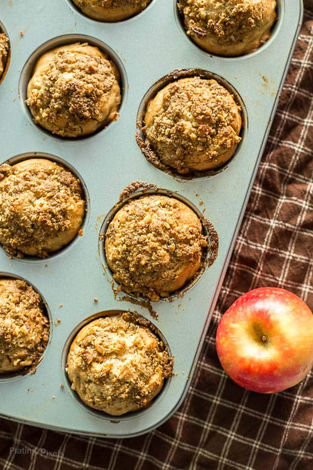 Lightened Up Apple Streusel Muffins in a muffin pan with an apple next to it